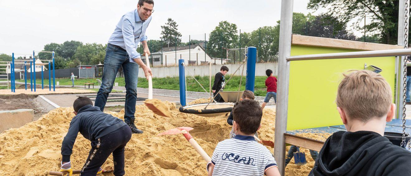 Einige Kinder und Oberbürgermeister Thomas Eiskirch helfen bei der Fertigstellung des Spielplatzes. Foto: Lutz Leitmann/Stadt Bochum